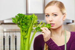 A mulher na cozinha guarda o aipo verde Imagens de Stock Royalty Free
