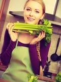 A mulher na cozinha guarda o aipo verde Imagem de Stock Royalty Free