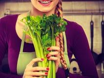 A mulher na cozinha guarda o aipo verde Foto de Stock