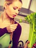 A mulher na cozinha guarda o aipo verde Fotografia de Stock Royalty Free