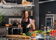 Mulher na cozinha moderna imagem de stock royalty free