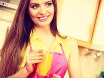 Mulher na cozinha que bebe o suco de laranja fresco Foto de Stock Royalty Free