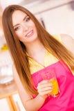 Mulher na cozinha que bebe o suco de laranja fresco Foto de Stock