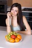Mulher na cozinha que come frutas Imagem de Stock Royalty Free