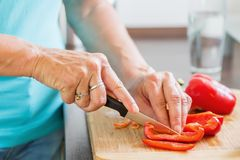 Mulher na cozinha que corta a pimenta vermelha Fotos de Stock