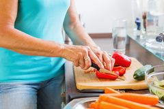 Mulher na cozinha que corta a pimenta vermelha Imagem de Stock