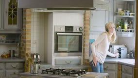 Mulher na cozinha que escuta a música em seus fones de ouvido que preparam e que esperam o café video estoque