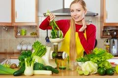 Mulher na cozinha que faz o suco vegetal do batido Fotografia de Stock