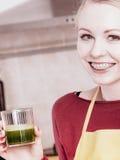Mulher na cozinha que guarda o suco vegetal do batido Imagem de Stock