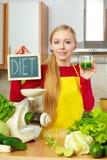 Mulher na cozinha que guarda o suco vegetal do batido Fotos de Stock Royalty Free