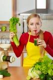 Mulher na cozinha que guarda o suco vegetal do batido do aipo Fotos de Stock