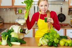 Mulher na cozinha que guarda o suco vegetal do batido do aipo Fotos de Stock Royalty Free