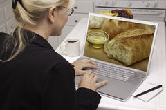 Mulher na cozinha usando o portátil - alimento e receitas Fotografia de Stock Royalty Free