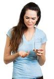 Mulher na dor que guardara a água e o comprimido foto de stock