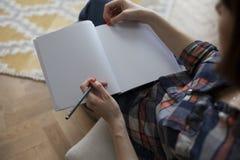 Mulher na escrita da camisa de manta no caderno vazio Imagem de Stock Royalty Free