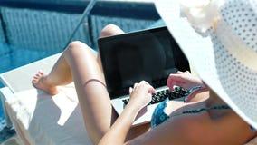 A mulher na escrita do chapéu do roupa de banho e do sol text usando o portátil que encontra-se na cadeira de plataforma perto da video estoque