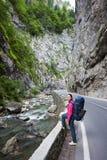 Mulher na estrada ao lado do córrego da montanha no desfiladeiro de Bicaz imagem de stock