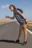 Mulher na estrada que espera um carro Fotografia de Stock