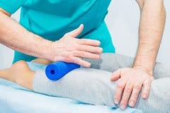 A mulher na fisioterapia que recebe a massagem do rolo do quiroprático do terapeuta A trata o pé paciente do ` s, caviar no escri fotos de stock