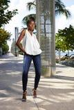 A mulher na fotografia instantânea afro-americano de calças de ganga magro entrega bolsos Fotos de Stock Royalty Free