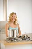 Mulher na frente de uma cozinha Fotografia de Stock