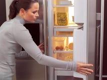 Mulher na frente do refrigerador aa Fotografia de Stock Royalty Free