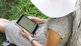 Mulher na grama com tabuleta video estoque