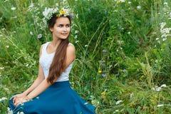 Mulher na grinalda dos wildflowers que sentam-se na grama Foto de Stock Royalty Free