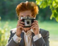 Mulher na idade de fotografar uma câmera do filme no parque fotos de stock royalty free