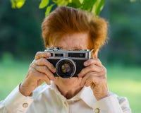Mulher na idade de fotografar uma câmera do filme no parque imagens de stock royalty free