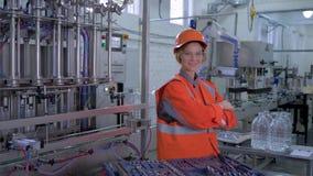 Mulher na indústria pesada, técnico feliz da fábrica fêmea no capacete de segurança que repara o equipamento e os sorrisos na pla video estoque