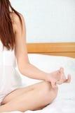 Mulher na ioga praticando da cama Imagem de Stock Royalty Free