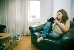 Mulher na leitura da cadeira Fotografia de Stock