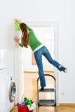 Mulher na limpeza da primavera que trabalha perigosamente Fotos de Stock