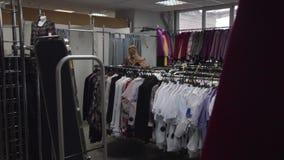 Mulher na loja de roupa video estoque