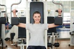 Mulher na máquina da imprensa do ombro no clube de aptidão imagem de stock royalty free