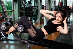 Mulher na máquina de enfileiramento e sentar-UPS no gym da aptidão Foto de Stock