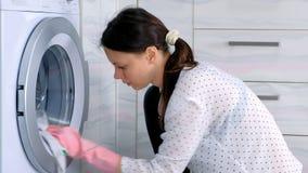 Mulher na máquina de lavar de borracha cor-de-rosa das lavagens das luvas com o pano, sentando-se no assoalho Vista lateral, clos