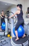 Mulher na máquina do instrutor na ginástica do esporte Imagem de Stock Royalty Free