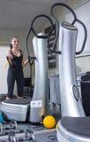 Mulher na máquina do instrutor na ginástica do esporte Fotografia de Stock Royalty Free