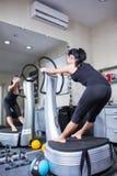 Mulher na máquina do instrutor na ginástica do esporte Fotografia de Stock