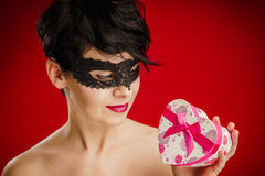 A mulher na máscara olha um presente Imagens de Stock Royalty Free