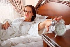 Mulher na mão de alargamento da cama ao despertador fotografia de stock