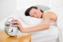 Mulher na mão de alargamento da cama ao despertador em casa Fotografia de Stock Royalty Free