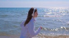 Mulher na música dos fones de ouvido que movimenta-se no treinamento exterior da corrida do esporte da praia da areia do mar vídeos de arquivo