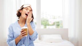 Mulher na m?scara do pijama e de olho com o caf? que boceja imagens de stock royalty free