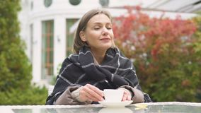 Mulher na manta que bebe o chá morno, apreciando a manhã do outono na jarda, conforto vídeos de arquivo