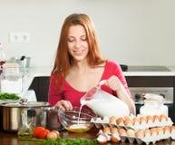 Mulher na massa de fatura vermelha ou omlet na cozinha Imagem de Stock Royalty Free