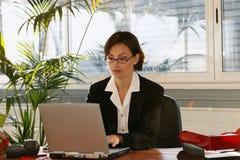 Mulher na mesa com computador portátil Fotografia de Stock