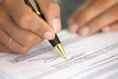 Mulher na mesa de escritório que assina um contrato com foco raso no si Fotos de Stock